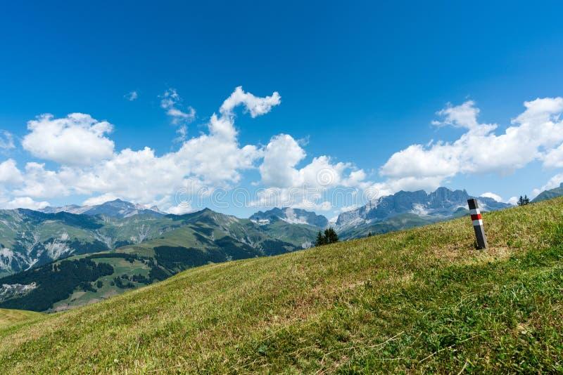 Paisaje idílico de la montaña con una pista de senderismo y un marcador del rastro en el primero plano y una gran visión imagen de archivo libre de regalías