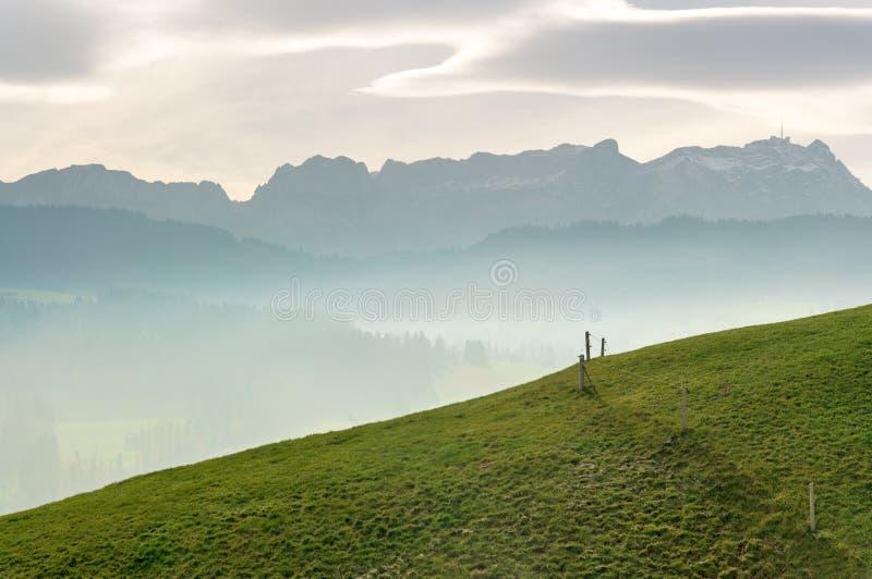 Paisaje idílico y pacífico de la montaña con una cerca de madera en una ladera herbosa y una gran vista de las montañas suizas de foto de archivo