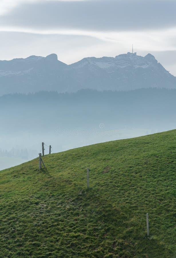 Paisaje idílico y pacífico de la montaña con una cerca de madera en una ladera herbosa y una gran vista de las montañas suizas de imágenes de archivo libres de regalías