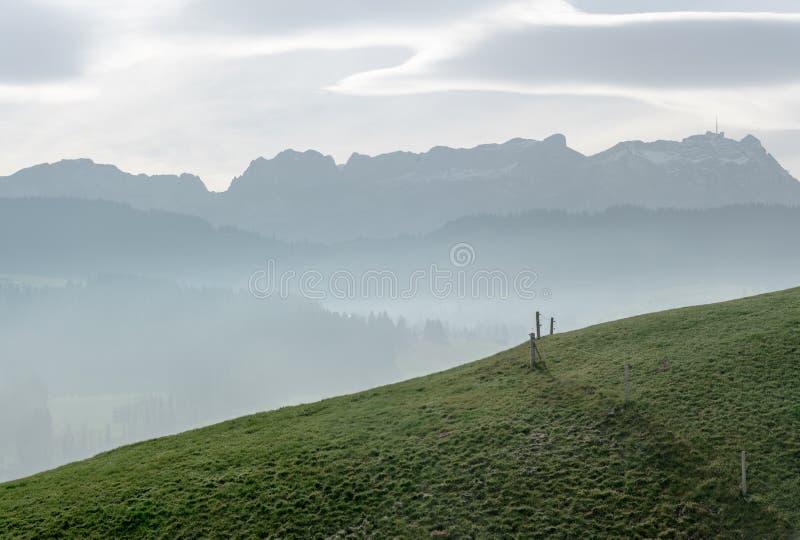 Paisaje idílico y pacífico de la montaña con una cerca de madera en una ladera herbosa y una gran vista de las montañas suizas de fotos de archivo libres de regalías