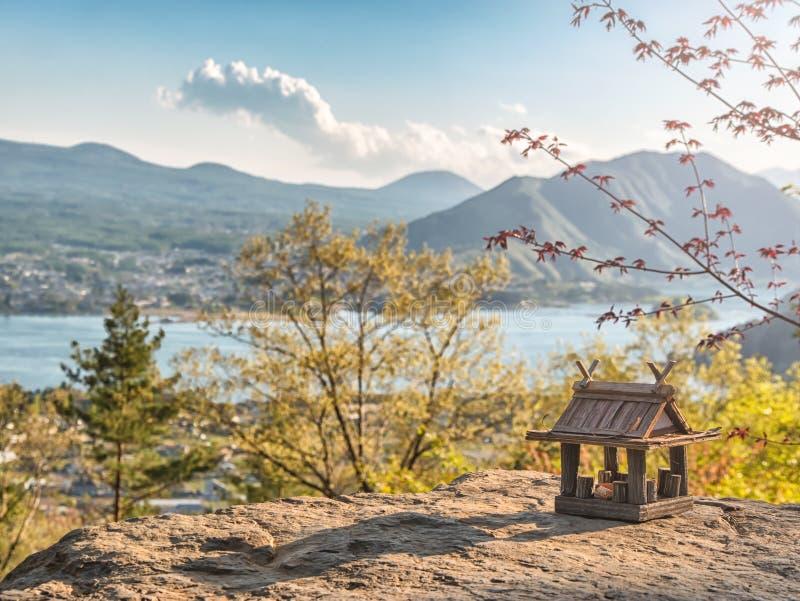 Paisaje id?lico en el Jap?n con la casa de madera tradicional del juguete y el lago hermoso con las monta?as en el fondo fotografía de archivo libre de regalías