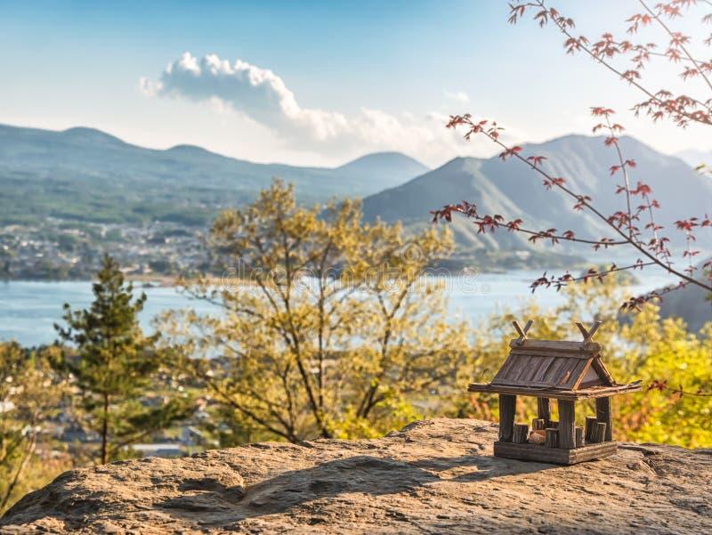 Paisaje id?lico en el Jap?n con la casa de madera tradicional del juguete y el lago hermoso con las monta?as en el fondo imagen de archivo libre de regalías