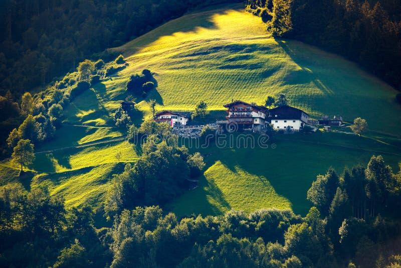 Paisaje iluminado por el sol fabuloso con los prados verdes, los árboles y los edificios típicos de las montañas imagen de archivo