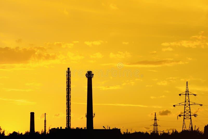 Paisaje industrial con las siluetas de tubos y de agains de las torres fotografía de archivo