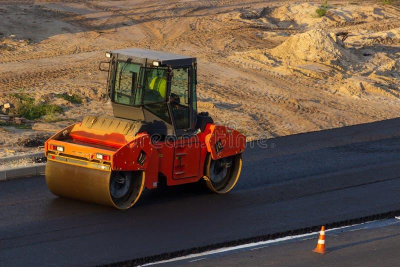 Paisaje industrial con los rodillos que rueda un nuevo asfalto en el camino Repare el trabajo, movimiento complicado del transpor foto de archivo libre de regalías
