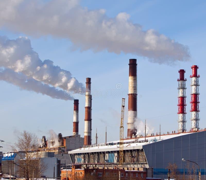 Paisaje industrial de la ciudad con los tubos que fuman y las líneas eléctricas en un día soleado claro fotos de archivo libres de regalías