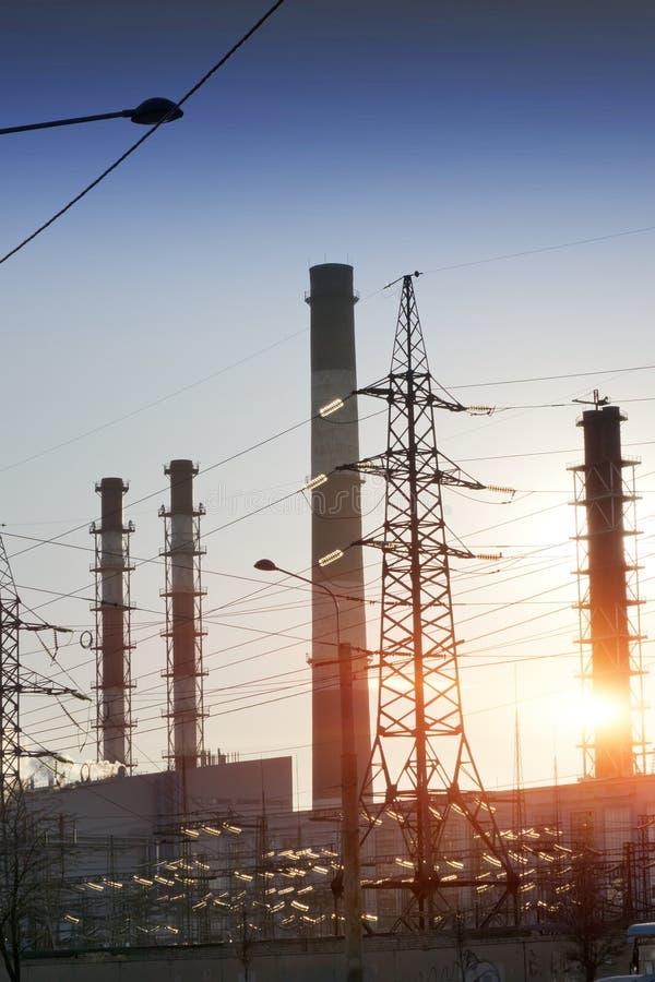 Paisaje industrial Puesta del sol sobre la línea eléctrica y los tubos de la central eléctrica del calor y combinada fotos de archivo