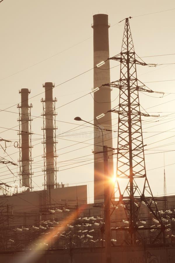 Paisaje industrial Puesta del sol sobre la línea eléctrica y los tubos de la central eléctrica del calor y combinada fotos de archivo libres de regalías