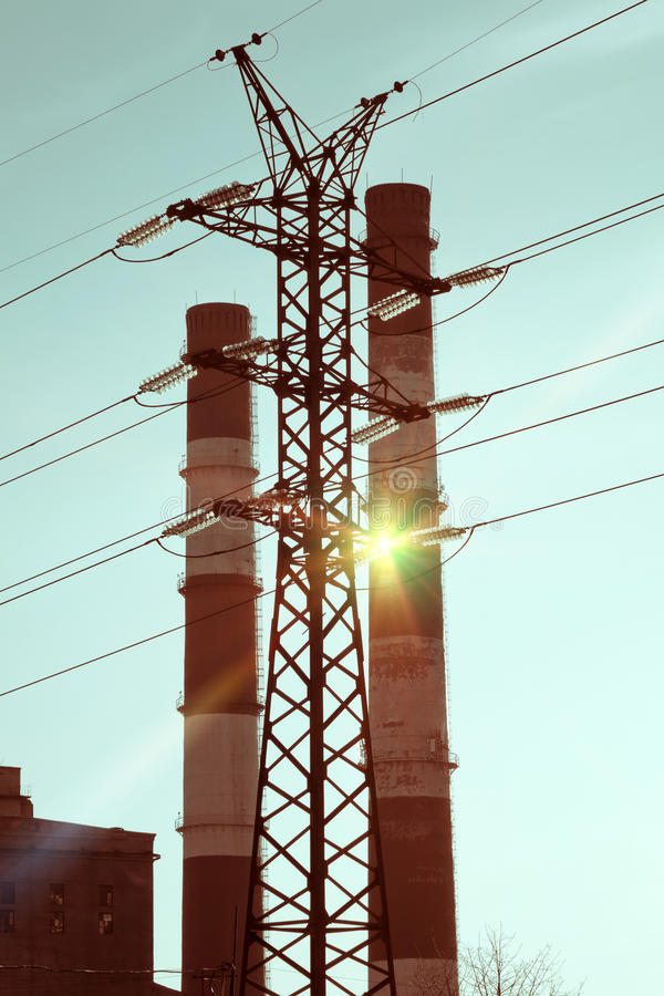 Paisaje industrial Puesta del sol sobre la línea eléctrica y los tubos de la central eléctrica del calor y combinada fotografía de archivo