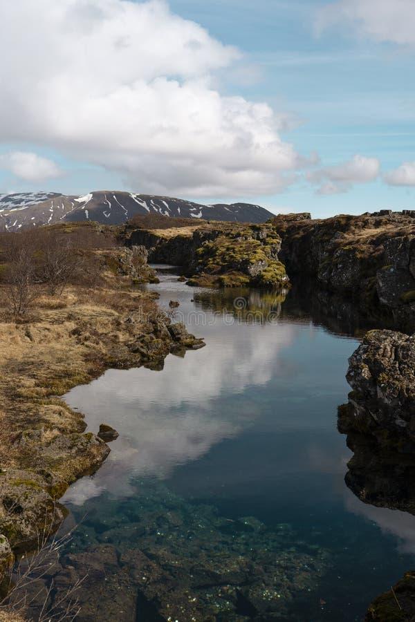 Paisaje islandés épico: un lago, acantilados, montañas, nubes, cielo azul imágenes de archivo libres de regalías