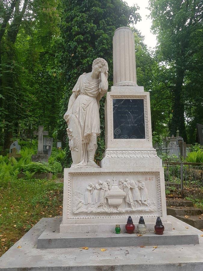 Paisaje La cripta antigua de la piedra blanca Hay una estatua de un individuo que se cerró los ojos con una mano e inclinados en  fotos de archivo