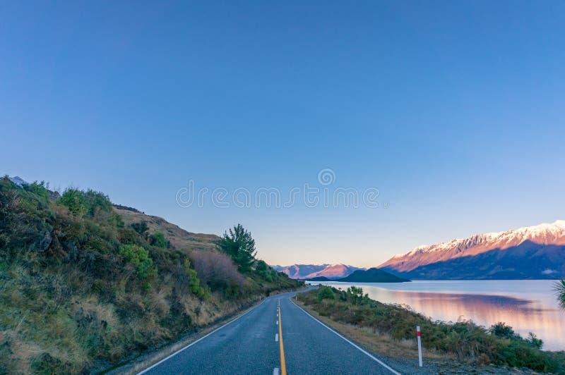 Paisaje largo de la carretera de asfalto con Mountain View y el lago fotos de archivo