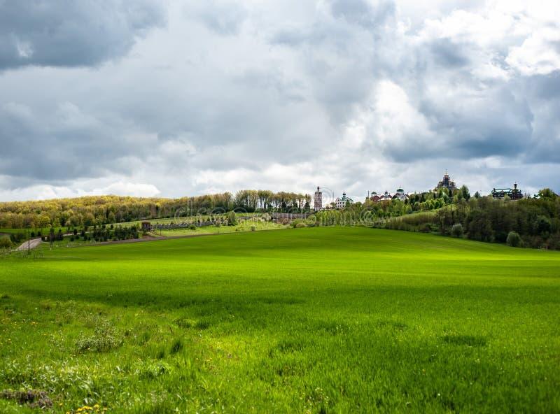 Paisaje llamativo con la hierba verde de la primavera, las colinas y los árboles, cielo nublado imagenes de archivo