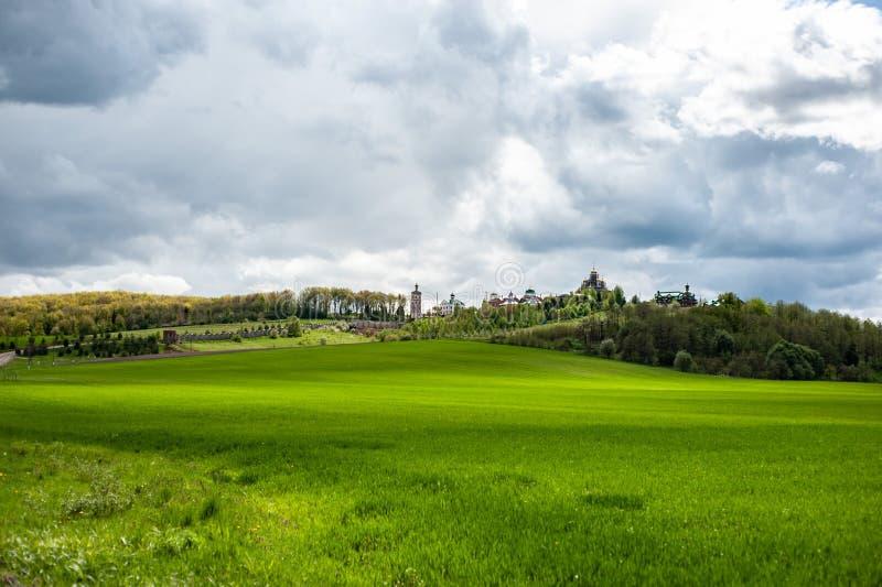 Paisaje llamativo con la hierba verde, las colinas y los árboles, cielo nublado fotos de archivo