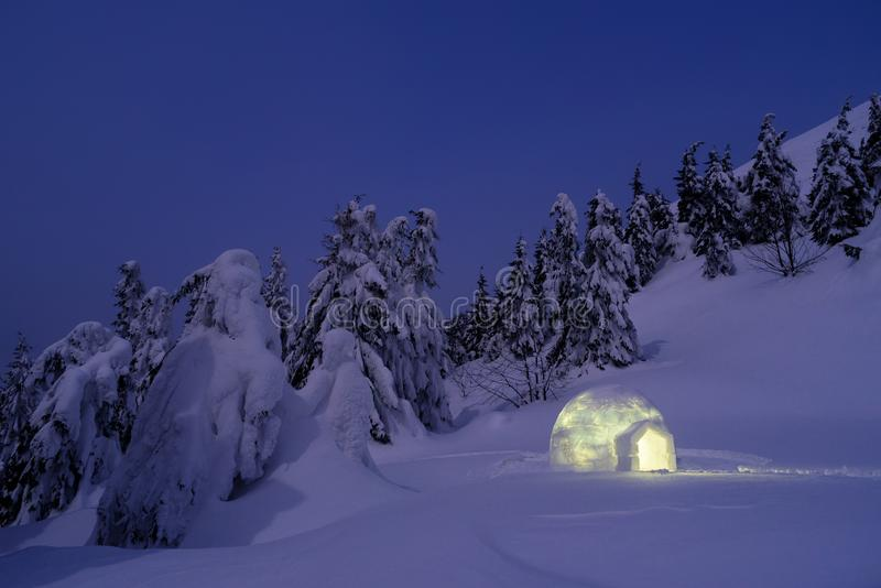Paisaje maravilloso con el iglú de la nieve en la noche imagenes de archivo