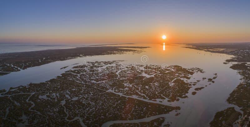 Paisaje marino aéreo de la puesta del sol en el parque natural de los humedales de Ria Formosa, canal marítimo interior Algarve imagenes de archivo