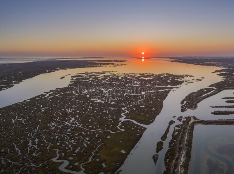 Paisaje marino aéreo de la puesta del sol en el parque natural de los humedales de Ria Formosa, canal marítimo interior Algarve fotos de archivo