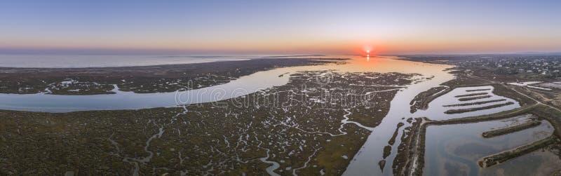 Paisaje marino aéreo de la puesta del sol en el parque natural de los humedales de Ria Formosa, canal marítimo interior Algarve foto de archivo libre de regalías