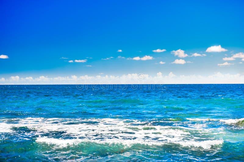 Paisaje marino con agua azul, el cielo y las nubes blancas fotos de archivo