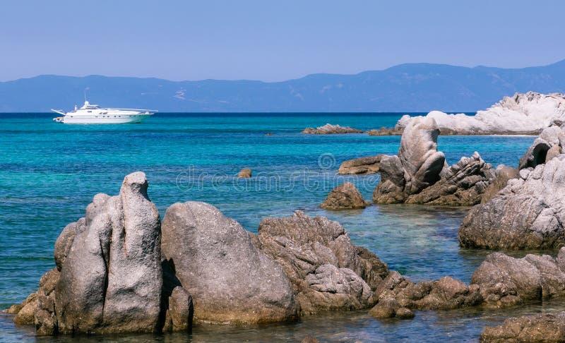 Paisaje marino con agua de la turquesa, el barco y las rocas hermosos del mar fotos de archivo