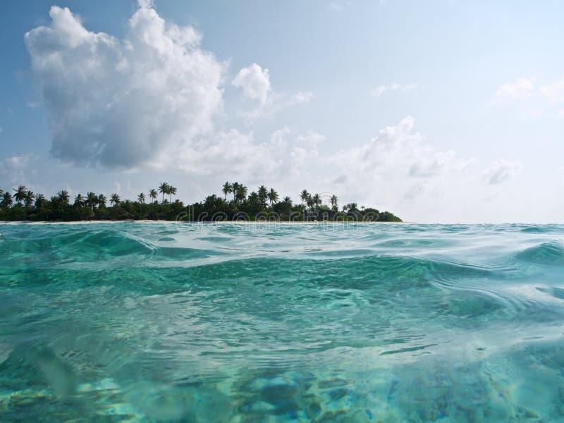 Paisaje marino con agua de la turquesa y los árboles tropicales en el horizonte foto de archivo