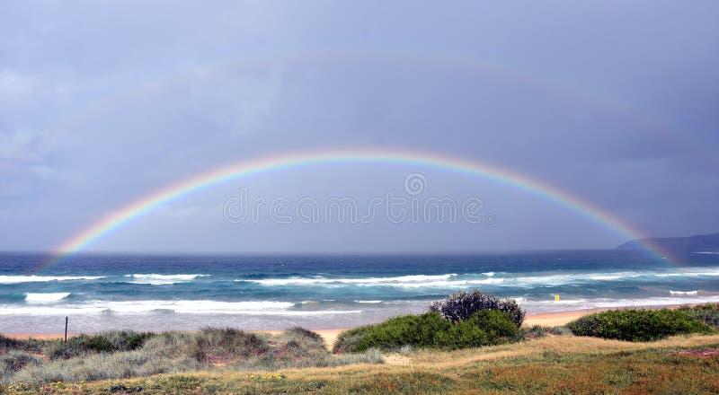 Paisaje marino con el arco iris multicolor hermoso sobre el mar imagen de archivo