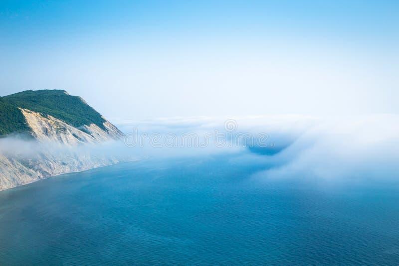 Paisaje marino con la costa rocosa y la nube que cuelga bajo sobre el agua imagen de archivo libre de regalías