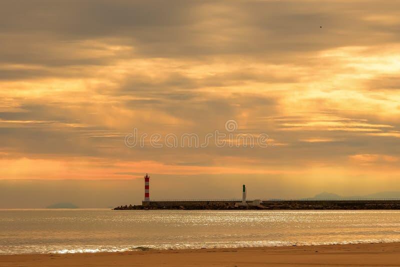 Paisaje marino con un embarcadero y un faro debajo de un cielo hermoso fotos de archivo