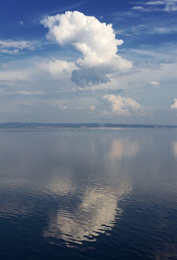 Paisaje marino con una nube blanca grande reflejada fotografía de archivo