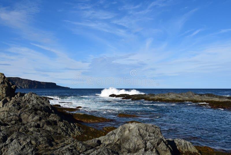 Paisaje marino de la costa de Killick con una onda que golpea una roca en el océano que hace un chapoteo grande fotografía de archivo