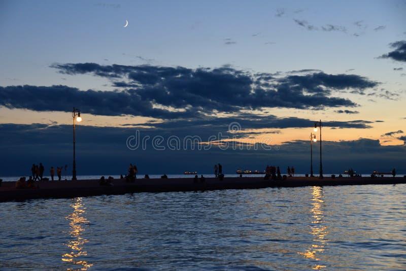 Paisaje marino de la noche con la gente que camina en un muelle fotos de archivo