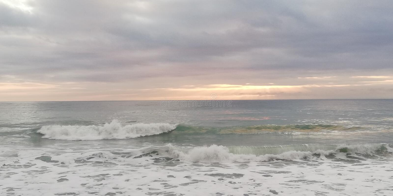 Paisaje marino de la puesta del sol El sol se rompe a trav?s de las nubes pesadas bajas imagen de archivo