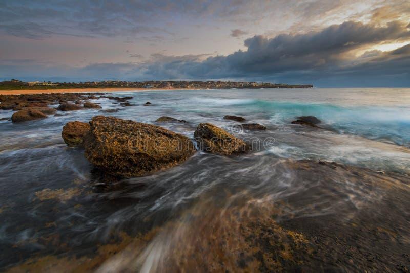 Paisaje marino de la salida del sol con la roca grande y agua que fluyen alrededor de ella imagen de archivo libre de regalías