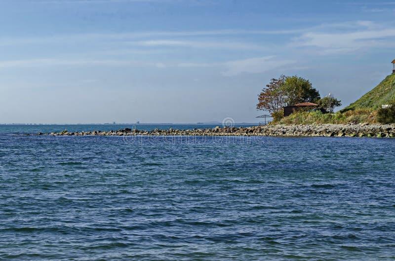Paisaje marino del embarcadero para pescar en el Mar Negro con el larus, la pequeña casa y el árbol en la costa, ciudad antigua N imagenes de archivo