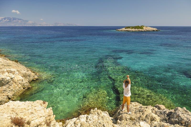 Paisaje marino del verano con el turista azul del mar y del varón en la costa costa fotos de archivo
