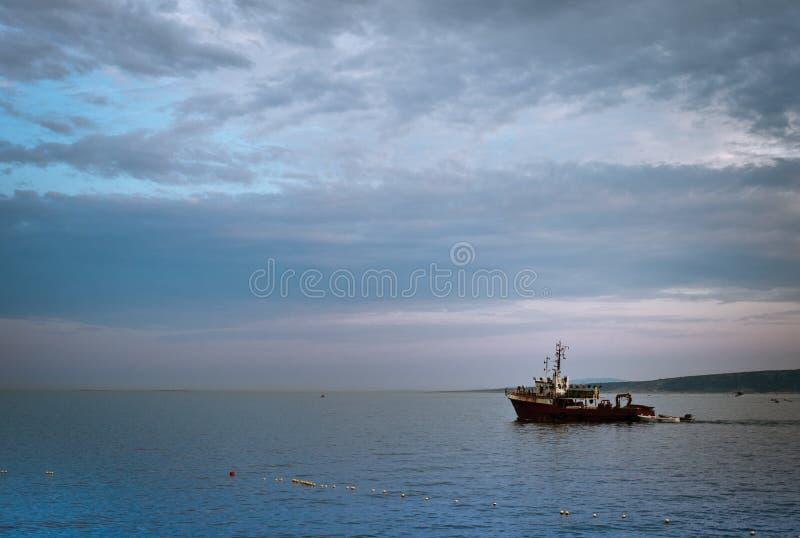 paisaje marino hermoso con las nubes y una navegación del barco de pesca al lado de las boyas foto de archivo libre de regalías
