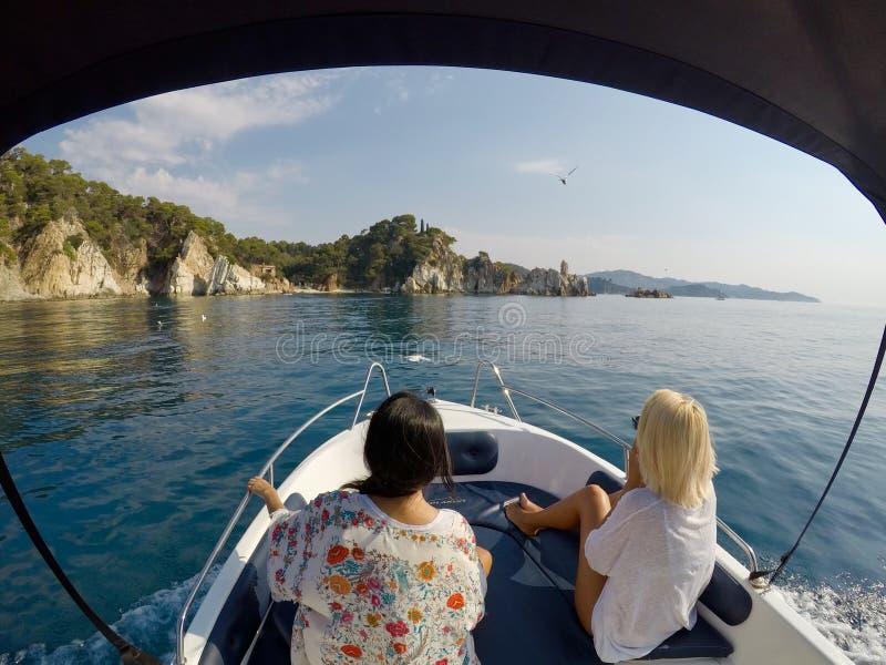 Paisaje marino hermoso de dos muchachas que navegan un barco de alquiler en el mar Mediterráneo en la España Costa Brava foto de archivo libre de regalías