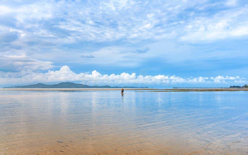 Paisaje marino hermoso de la calma con el pescador en cielo azul nublado imágenes de archivo libres de regalías