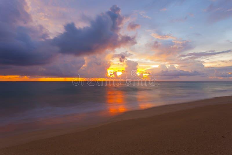 Paisaje marino hermoso de la puesta del sol con las nubes coloridas del cielo dramático y foto de archivo
