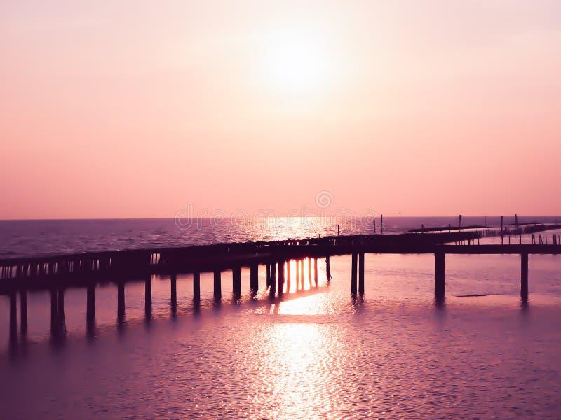 Paisaje marino hermoso del verano de Tailandia, cielo rosado en la puesta del sol, mar caliente, puente de madera en fondo de sen imagen de archivo libre de regalías