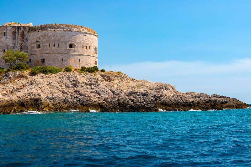 Paisaje marino increíble Torre vieja en una orilla rocosa por el mar, bahía de Boka-Kotor, foto de archivo