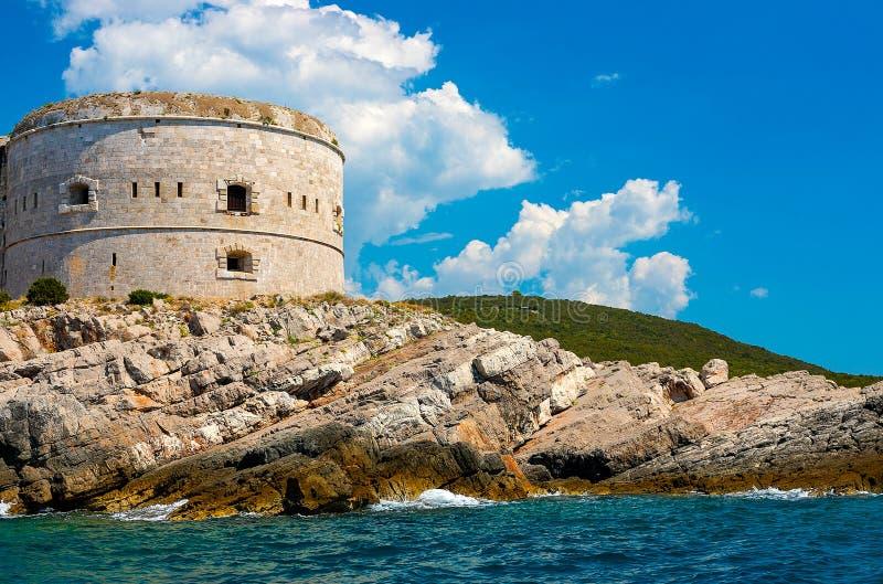 Paisaje marino increíble Torre vieja en una orilla rocosa por el mar, bahía de Boka-Kotor, imagen de archivo