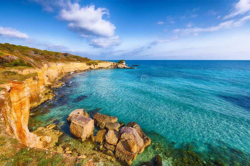 Paisaje marino pintoresco con los acantilados, la bahía del mar, los islotes y el faraglioni rocosos blancos cerca por el della P fotografía de archivo