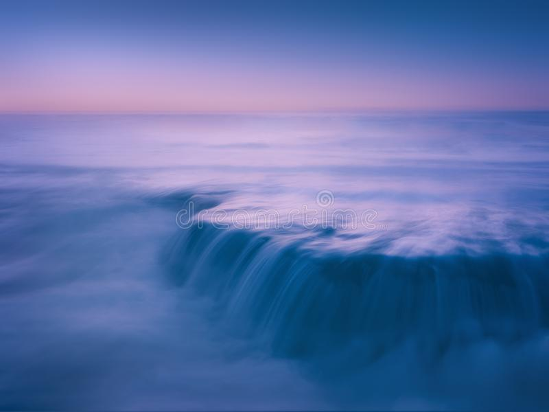 Paisaje marino soñador y hermoso con la roca y exposición larga en bea foto de archivo