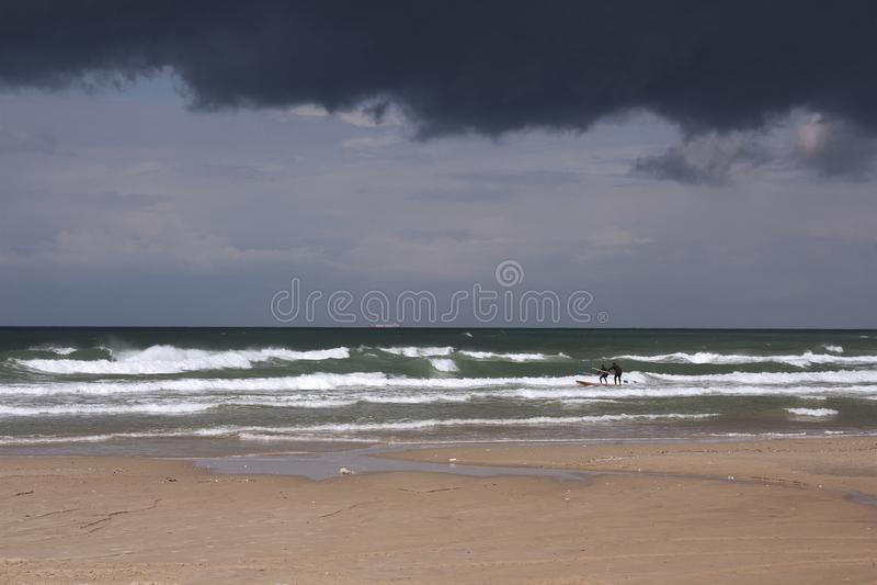 Paisaje marino tempestuoso con dos hombres del tablero de paleta imagen de archivo