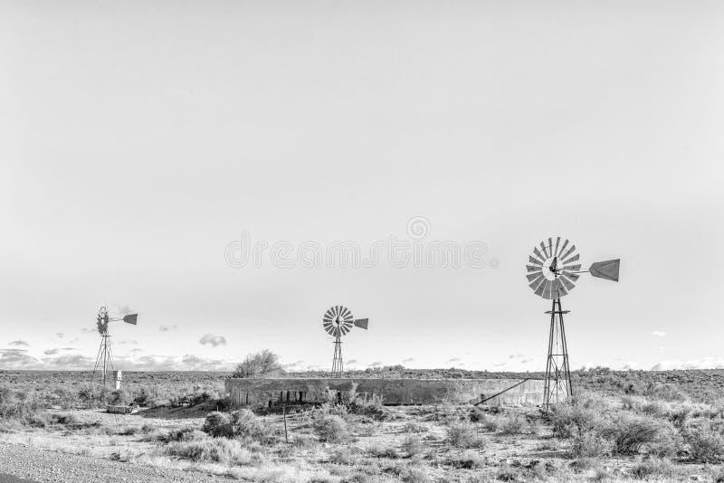 Paisaje monocromático con tres molinoes de viento y presas del bombeo de agua fotografía de archivo