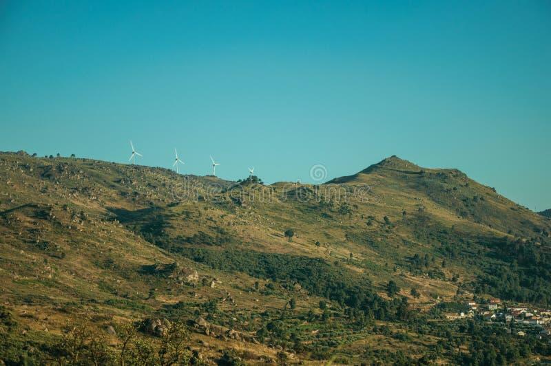 Paisaje montañoso cubierto por las rocas y algunas turbinas de viento fotografía de archivo