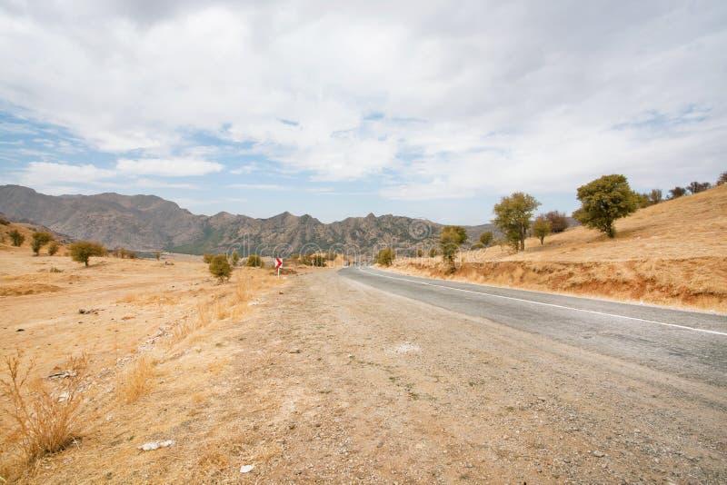 Paisaje natural con una carretera de asfalto entre los pueblos rodeados por las montañas foto de archivo