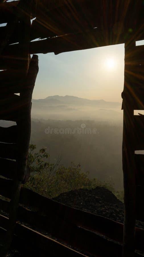 Paisaje natural en la salida del sol en verano con las ventanas de madera como marcos foto de archivo libre de regalías