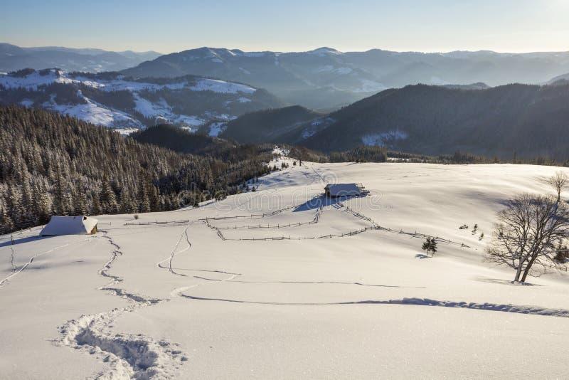 Paisaje navideño de invierno en el valle de montaña en un día helado y soleado Vieja cabaña de pastor abandonada de madera con ni imagen de archivo